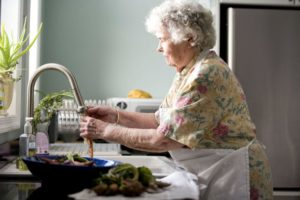 elderly-woman-in-kitchen-in-process-of-food-preparation-725x483